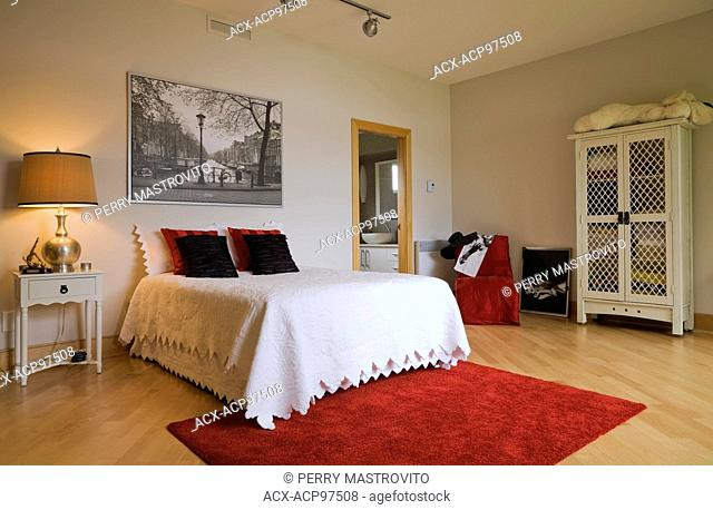 Queen size bed and white wooden armoire with lattice frames in a guest bedroom on the upstairs floor inside a modern cubist style residential home, Quebec