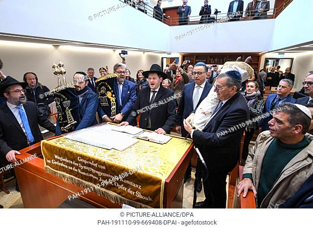 10 November 2019, Baden-Wuerttemberg, Konstanz: The board of the Jewish community in Konstanz and Baden hold three Torah rolls in their hands and then place...
