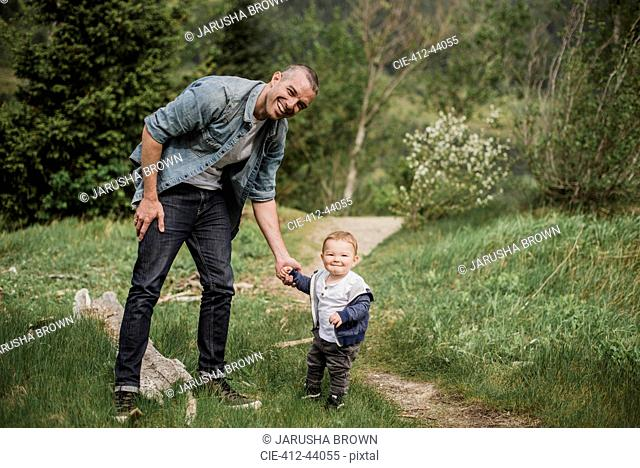 Portrait father and baby son walking on grassy path