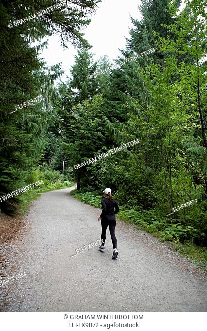 Woman running at Lost Lake trails Whistler, British Columbia
