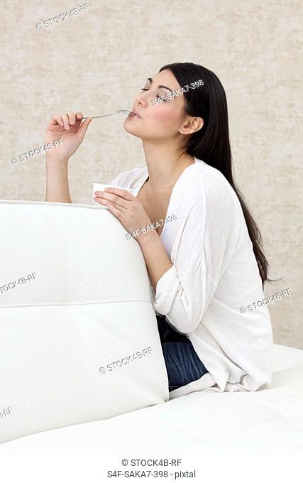 Dark-haired young woman eating yogurt