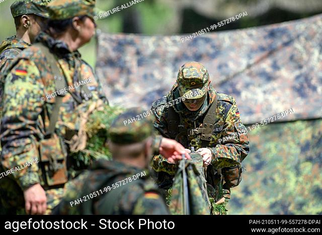 11 May 2021, Saxony-Anhalt, Burg: Recruits of the logistics battalion 171 practice tent construction on the site training area