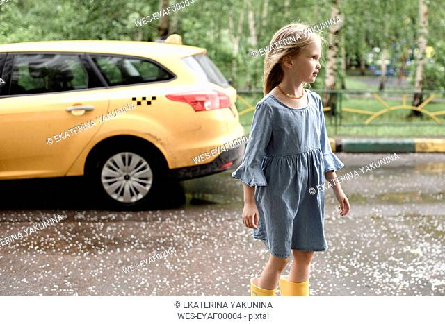 Girl wearing blue dress and vrossing road, yellow car in the background