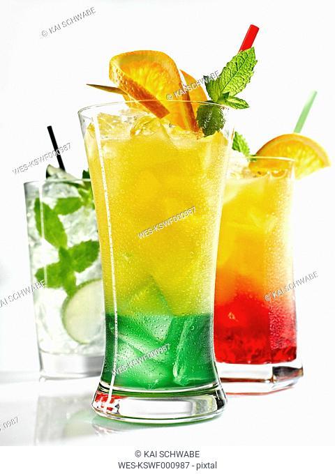 Glasses of iced orange juice, tequila sunrise and mojito on white background