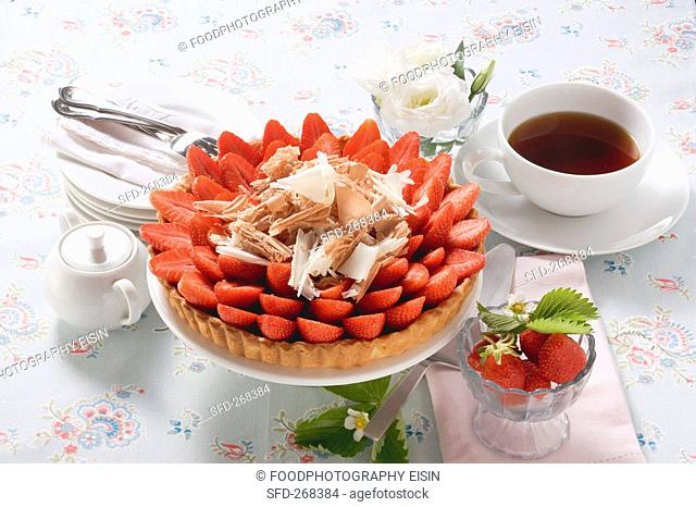 Strawberry tart with chocolate shavings, cup of coffee