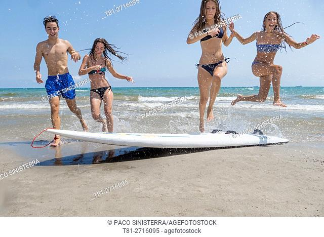 group of girls and boy running on the beach in Castellon. Spain
