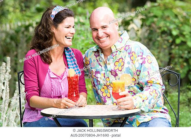 Close-up of a mature couple sitting at a table and holding glasses of juice