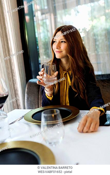 Smiling woman sitting at table in a restaurant drinking glass of water