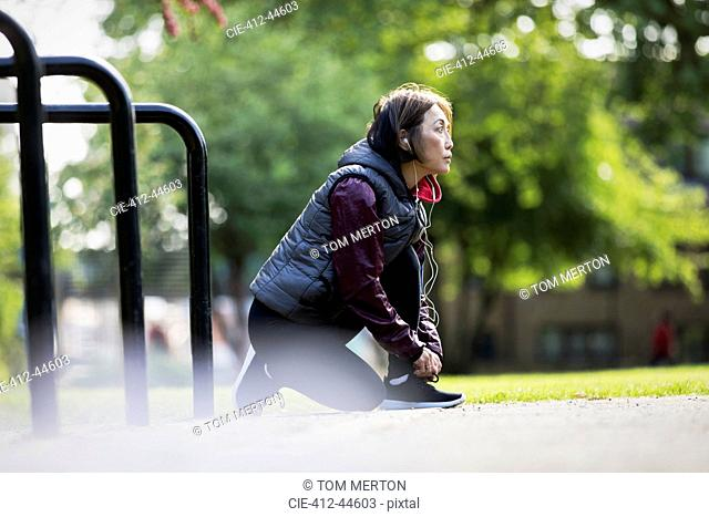 Active senior female runner with headphones tying shoe in park