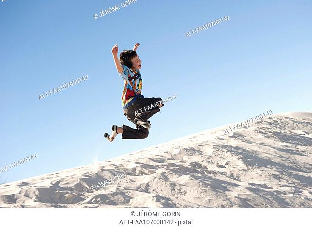 Boy jumping in midair over dune at White Sands National Monument, New Mexico, USA