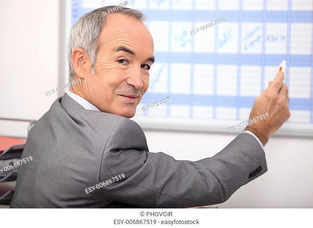 Grey haired man writing on calendar
