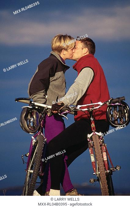 Couple sitting on bikes and kissing
