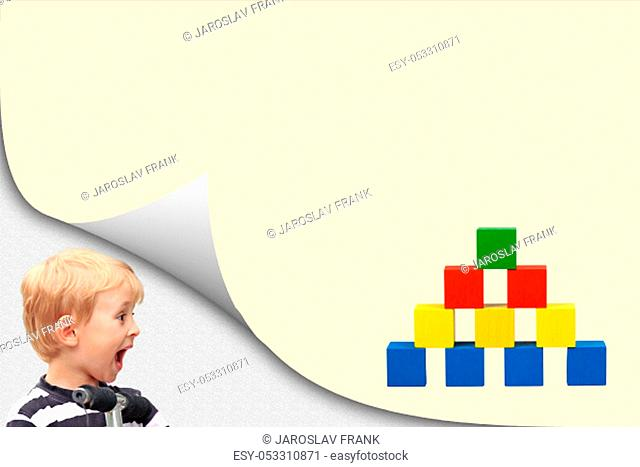 Surprised blond boy in an exposed corner is looking at blank yellow page with colorful wooden cubes toy pyramid
