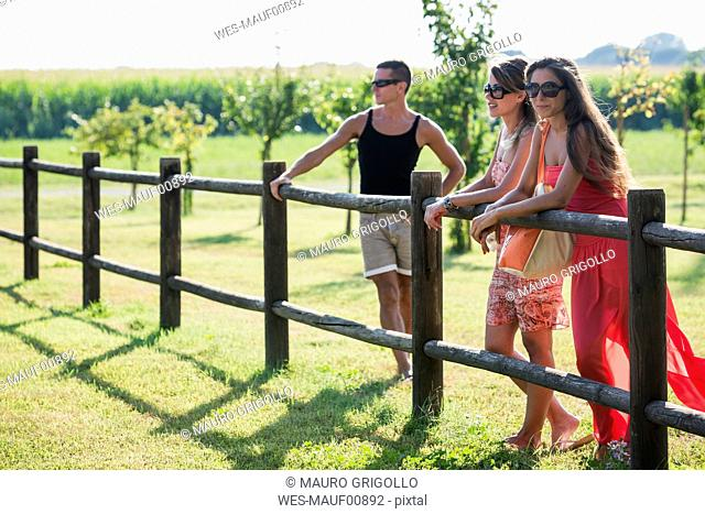 Three friends standing at wooden fence