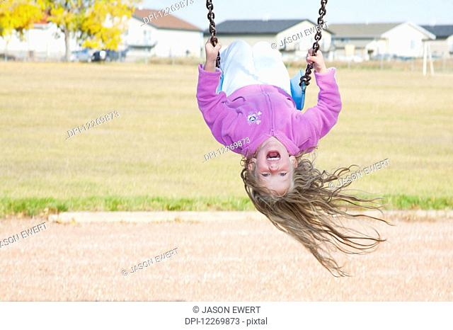 Young girl on swing in a playground in residential community on a cool, windy fall day; Three Hills, Alberta, Canada