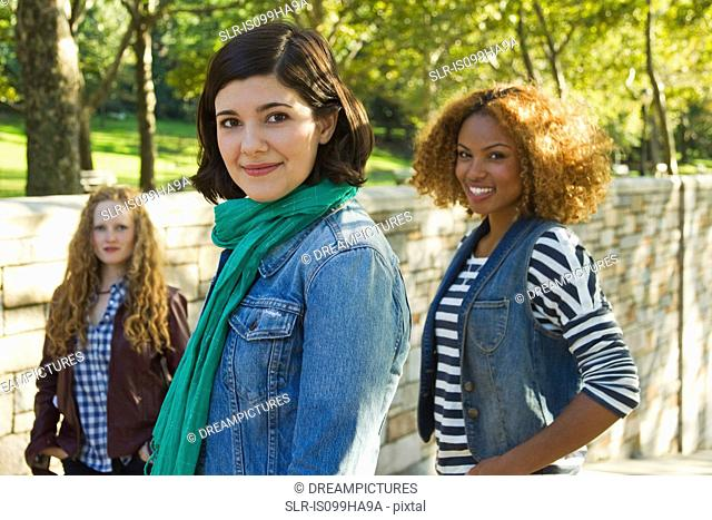 Three friends standing together in park, portrait