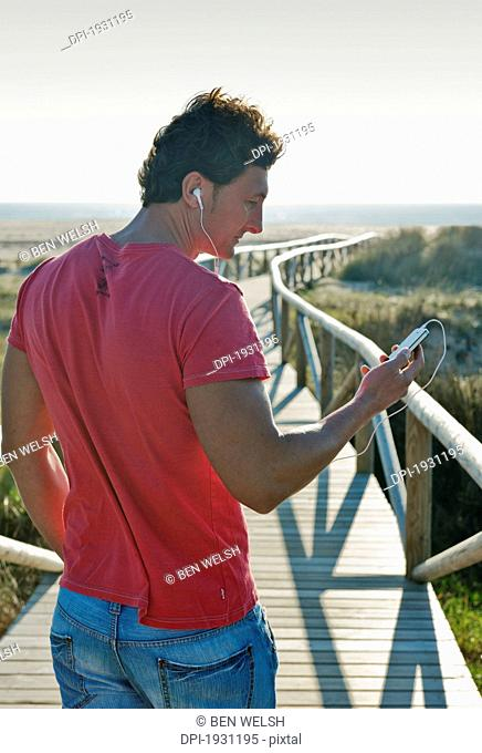 a man listening to music with earbuds as he walks down a wooden promenade towards dos mares beach, tarifa, cadiz, andalusia, spain