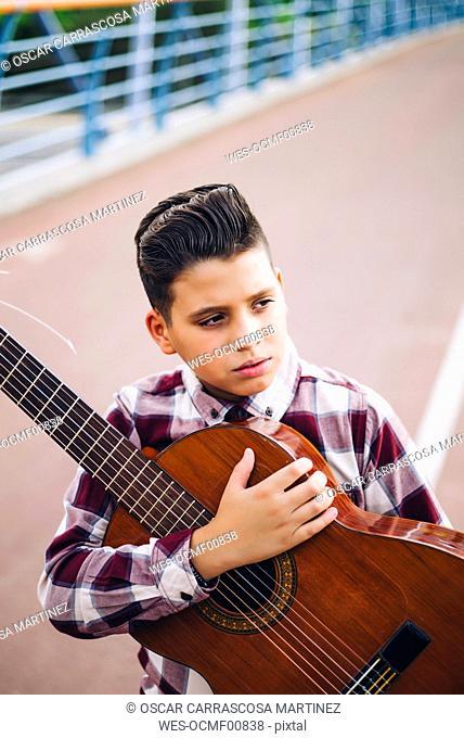 Gypsy boy with guitar on a bridge