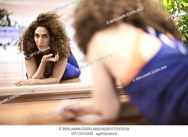 sporty mature woman laying on floor in fitness studio, looking at herself in mirror