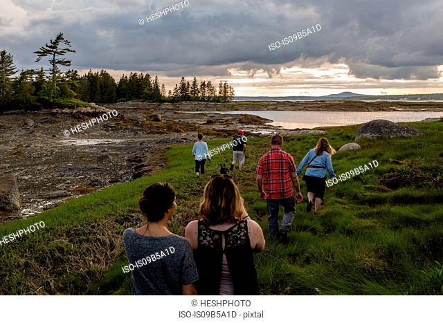 Rear view of adult family walking to coast in Maine, USA