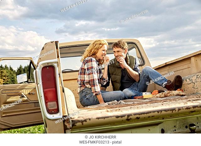 Couple sitting on pick up truck having a picnic