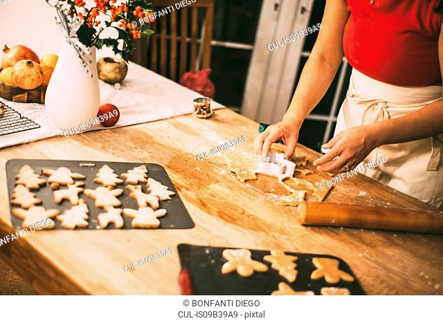 Mid section of woman cutting Christmas cookie shapes at kitchen counter