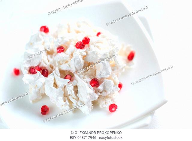 Portion of meringue with pomegranate seeds