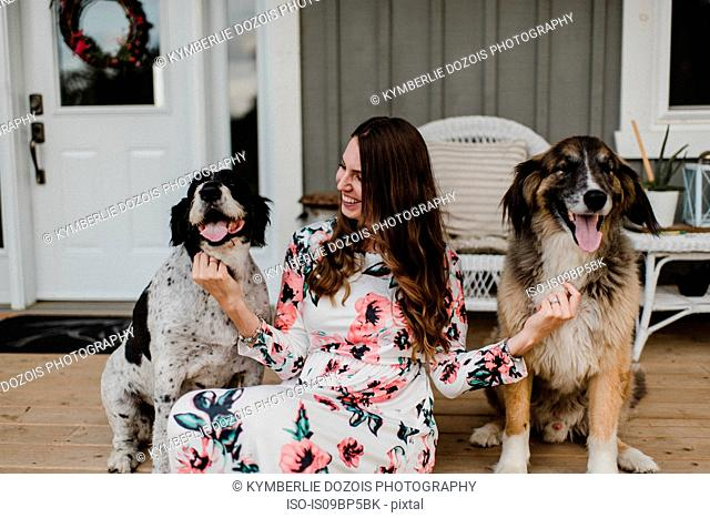 Woman and her two dogs sitting on porch