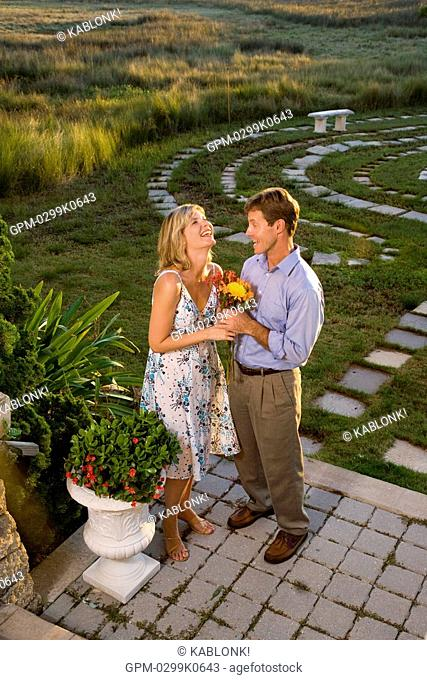 High angle view portrait of young couple holding flowers in outdoor garden