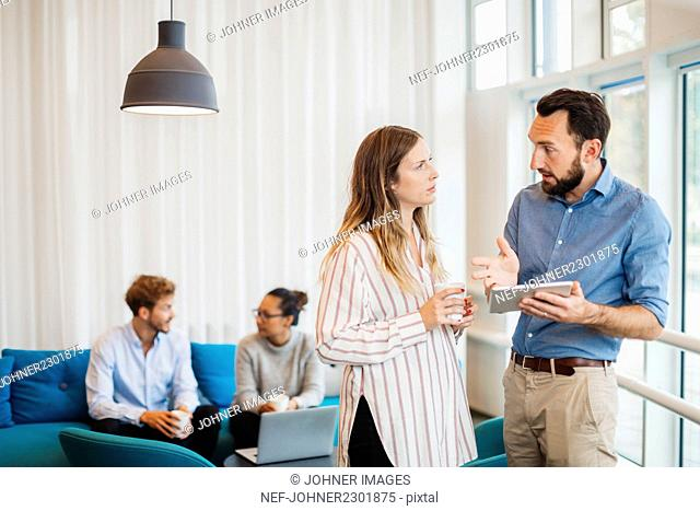 Four friends talking in living room