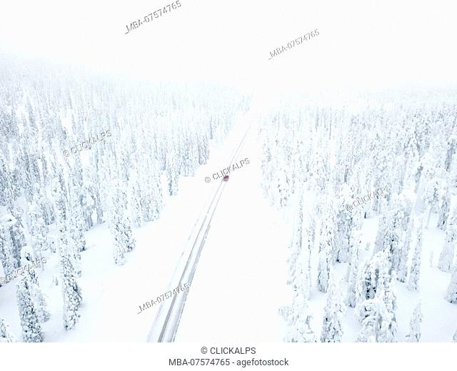 Aerial view of car along the snowy road in the icy forest, Pallas-Yllastunturi National Park, Muonio, Lapland, Finland