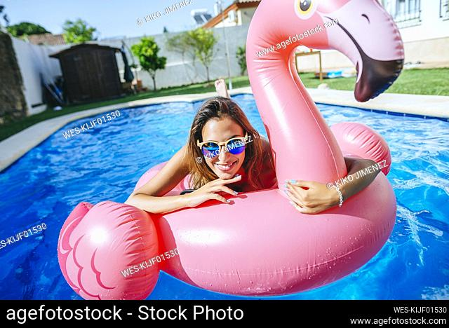 Portrait of happy young woman with pink flamingo float in swimming pool