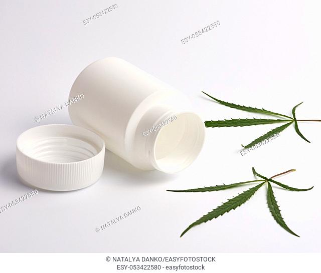 open empty white plastic medical jar for pills and green hemp leaf on a white background, alternative medicine concept