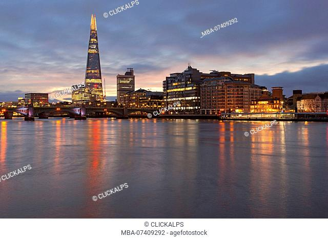 Southwark area with Shard and Southwark bridge reflected in river Thames during a cloudy dawn, London, Great Britain, UK