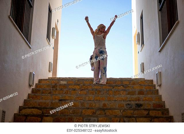 woman celebrating on a flight of stairs between two buildings outlined against the blue sky raising her arms outstretched in the air