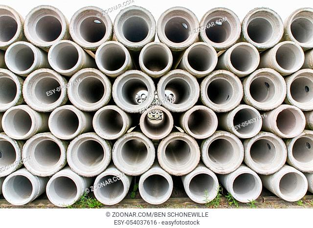 Pile of concrete sewer pipes on concrete plant grounds