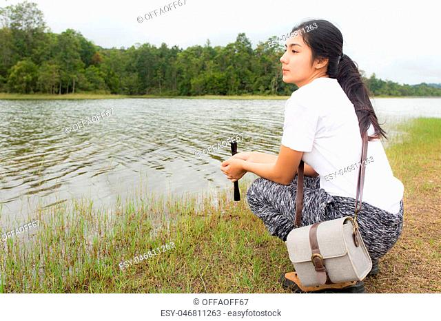 Young asian woman using binoculars in the topical forest