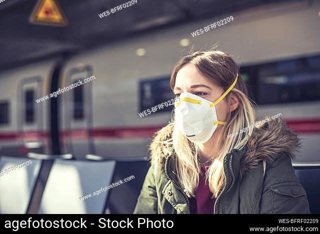 Portrait of young woman wearing respirator mask at station platform