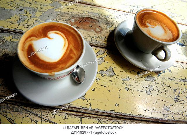 Cups of hot flat white coffee drinks on an old wooden table in a cafe
