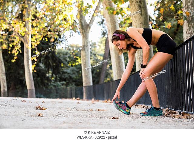 Fit young woman stretching before training