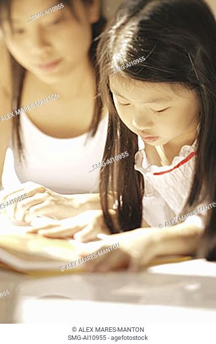 Mother and daughter, side by side, looking at magazine