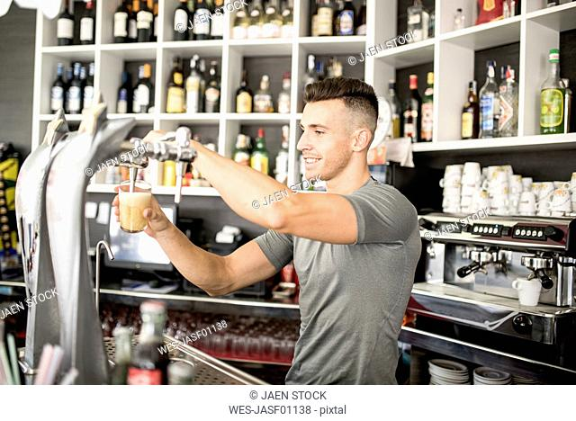 Smiling barkeeper tapping beer