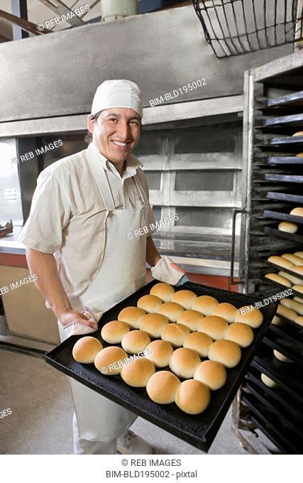 Hispanic baker holding tray with bread