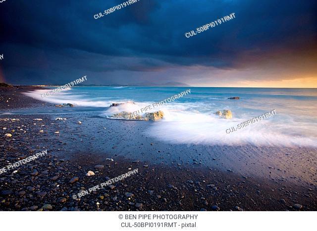 Waves washing up on sandy beach