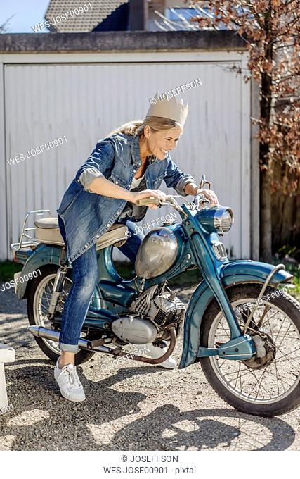 Happy woman on vintage motorcycle wearing a crown