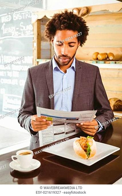 Businessman reading newspaper while having lunch