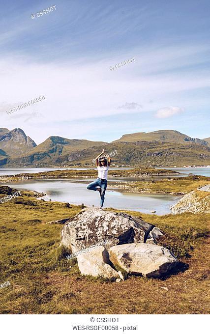 Norway, Lofoten, young woman standing on a rock on one leg doing yoga