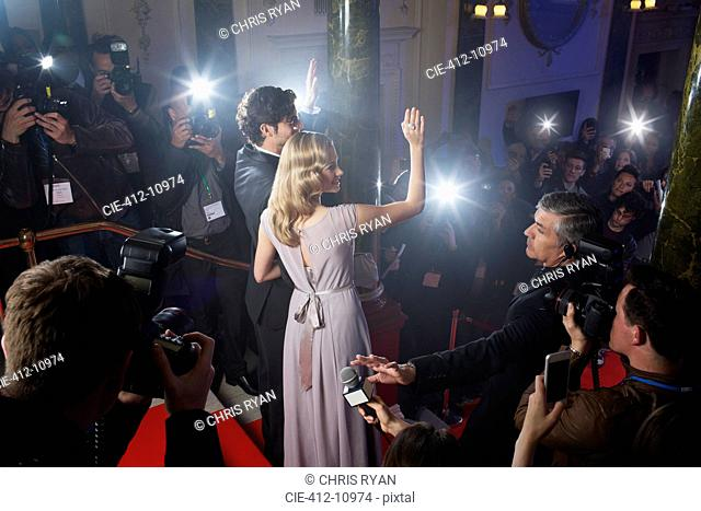 Celebrity couple waving to fans and paparazzi on red carpet
