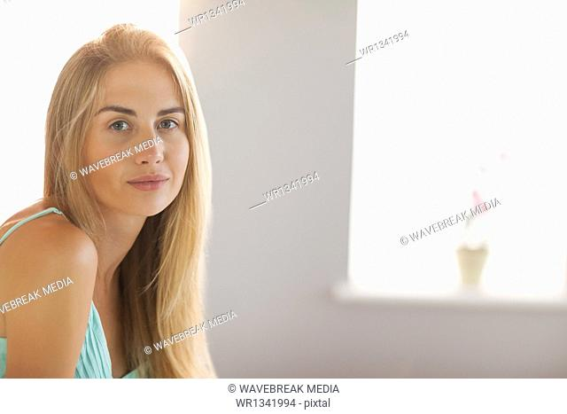 Smiling blonde woman sitting on her bed