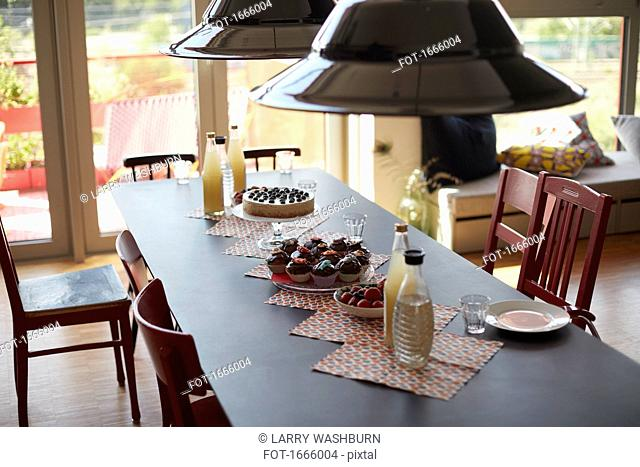 High angle view of pendant lights hanging over food served on dining table at home
